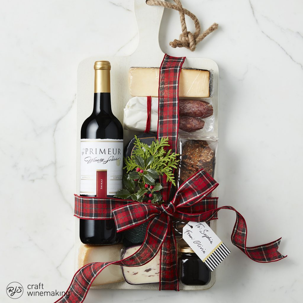 Primeur bottle of wind wrapped in a ribbon with cheese and summer sausage.