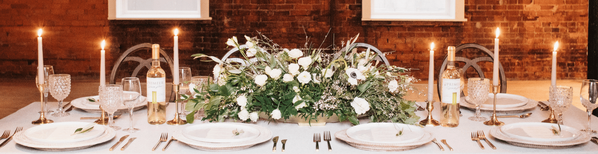 long wedding table set with candles and flower in front of a brick wall.