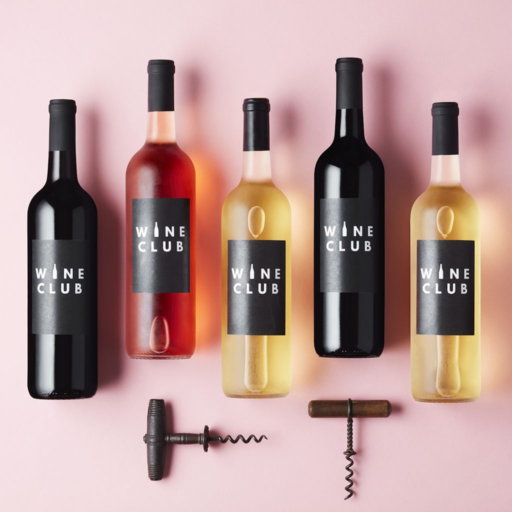 row of different wine bottles on a pink background
